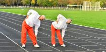 Two retired people stretching on a track